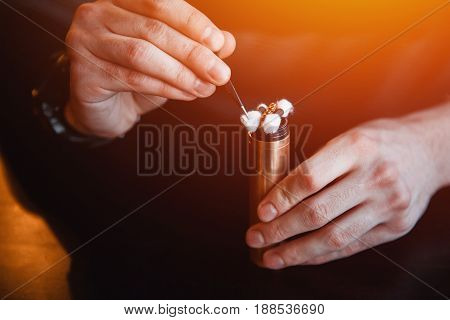 Vape.male master holds scissors, cotton wool and an electronic cigarette on a dark wood background.vaping device