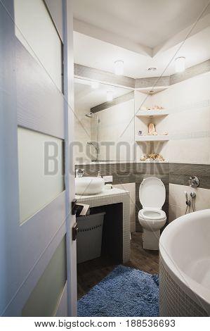 Interior design of a luxury bathroom, washroom with washbasin (sink), bathtub, huge mirror and seashells on the counter. Vertical