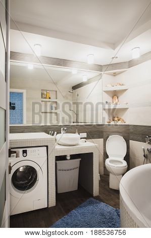Bathroom with lavatory pan, hygienic shower, modern style sink and laundry washer. Scandinavian interior design of water closet.