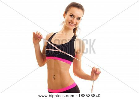 Cheerful young sports woman with measure tape smiling on camera isolated on white background