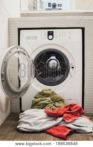 Washing machine with multicolored dirty towels on the floor near it. laundry washer with opened door. Frontal view. Vertical