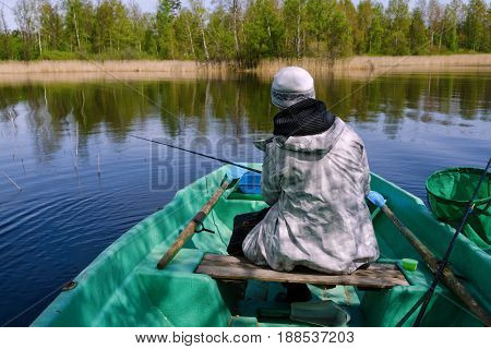 A fisherman woman sits with a fishing rod in a boat. Waiting for a fish bite. In the background, you can see the shore of the lake.