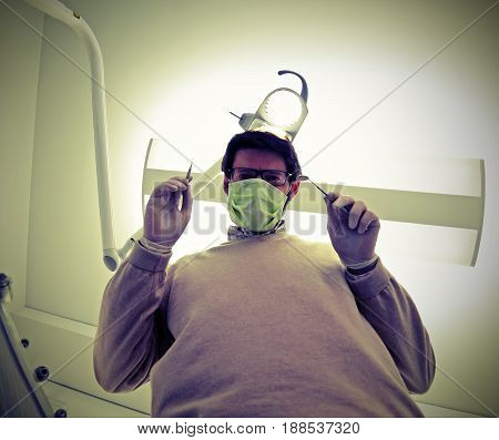 Dentist With Green Health Mask And Tooth Care Equipment In The D