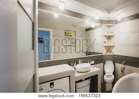 Interior design of a luxury bathroom, washroom with washbasin (sink), bathtub, huge mirror and seashells on the counter. Horizontal