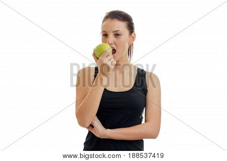 Beautiful young brunette eats green apple isolated on white background