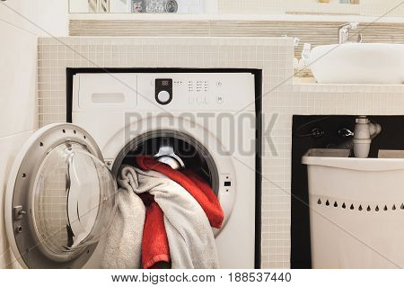 Washing machine with multicolored dirty towels inside. Horizontal