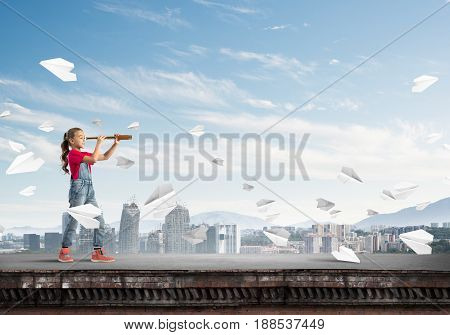 Cute kid girl standing on house roof and looking in spyglass
