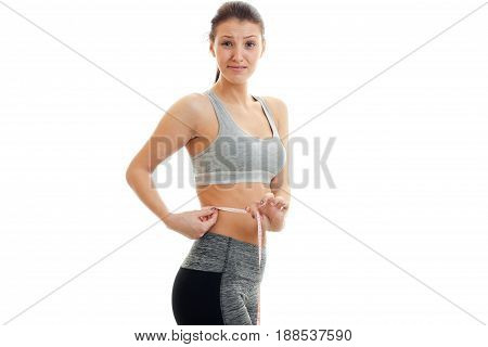 surprised young woman in sports uniform measure her waist with a tape isolated on white bakground