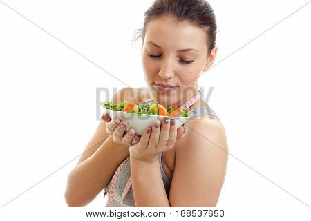 portrait of beautiful young woman with diet food in plate isolated on white bakground
