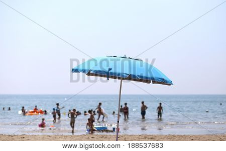 Sun Umbrella And Many People Playing In The Sea Water In Summer
