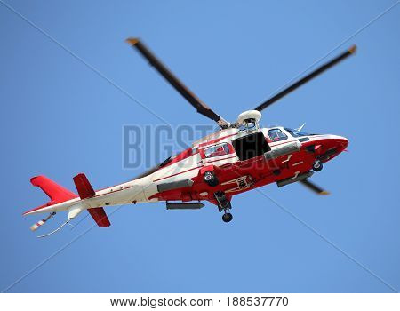 Relief Helicopter Flies Fast In The Blue Sky During The Emergenc