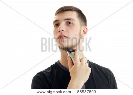young man shaving his bears with a trimmer isolated on white bakground