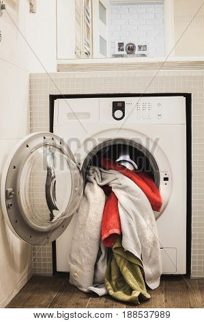 Washing machine with multicolored dirty towels inside. laundry washer with opened door filled by clothes. Vertical