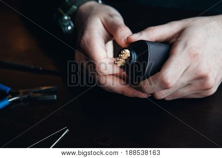male master installs a coyle. Spiral for electronic evaporator and cigarette. Vape, vaping. Pliers, wire, fichral, coil, screwdriver