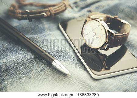 man watch phone and pen on jeans