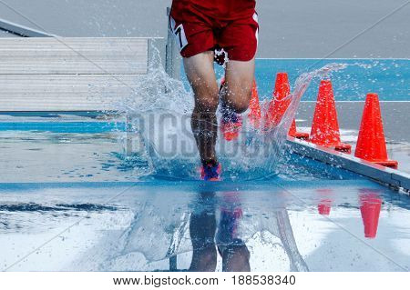 Landing and splashing in water while racing in the steeplechase