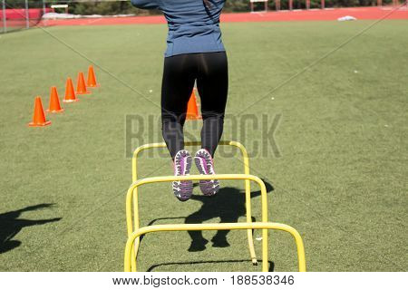 high school girls doing agility drills over yellow hurdles and orange cones on a green turf field during track and field practice.
