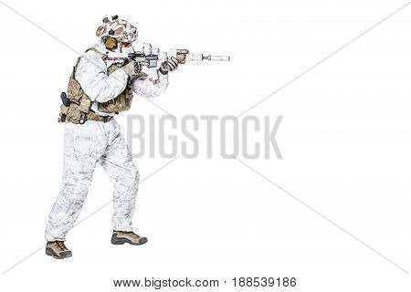 Special forces operator of Navy Seals armed with assault rifle with closed face in polarized sunglasses and military winter camo clothes designed to operations in extreme conditions. Studio shot