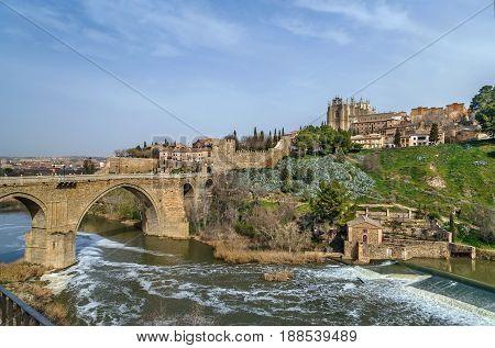 Panoramic view of Monastery of San Juan de los Reyes (Monastery of Saint John of the Monarchs) with bridge over Tagus river Toledo Spain