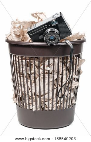 Old film camera in a trash bin full of toilet paper, isolated on a white background