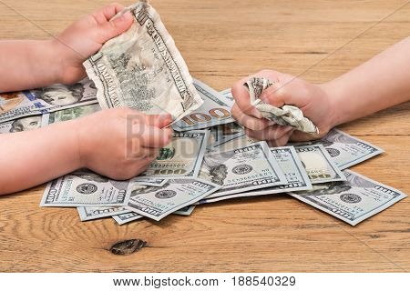 Children play real money on the wooden floor by squeezing them with their hands, close-up