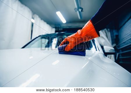 Worker hand in the glove holds a soapy sponge cleaning white car. Concept manual car wash for cars.