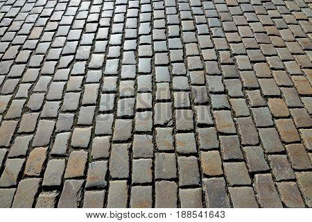 Antique cobblestone road shined bright sun. Stone background