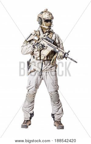 Army soldier in Protective Combat Uniform holding Special Operations Forces Combat Assault Rifle. Knee pads, mag recovery pouch, chest rig, military boots. Studio shot, isolated on white background