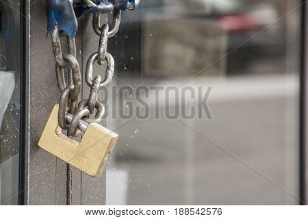 Brass Padlock And Chain On A Glass Door