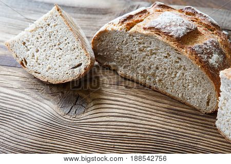 A freshly baked rustic loaf of bread on an old wooden table
