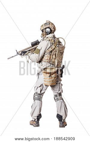 Army soldier in Protective Combat Uniform holding Special Operations Forces Combat Assault Rifle. Knee pads, mag recovery pouch, chest rig, military boots. Studio shot, isolated on white, back view