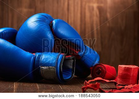 Close-up of the blue boxing gloves and red bandage on wooden background. Horizontal photo of the bright colorful sportwear and sportive accessories. Sportive background and still-life. Concept of the sportive healthy lifestyle.