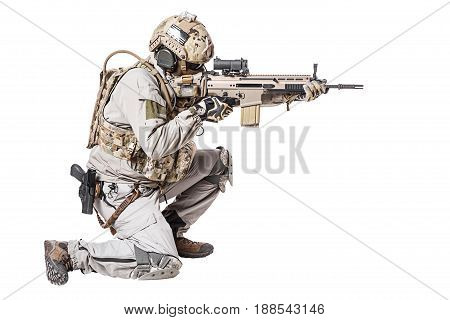 Army soldier in Protective Combat Uniform holding Special Operations Forces Combat Assault Rifle. Shooting weapon in kneeling position. Studio shot, isolated on white background