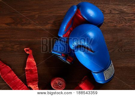 Top view of red boxing gloves and bandage on brown wooden plank background. Sportive exercise and training. Colorful sportwear and sportive accessories. Horizontal photo. Concept of the active sportive lifestyle.