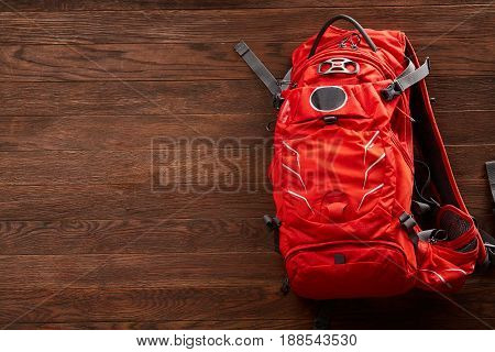 Top view of the bright orange travel backpack on a wooden background. Equipment for travel. Planning and preparation for the trip. Trip around the world. Close-up and horizontal photo. Concept of active lifestyle.