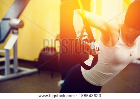 close-up girl is engaged with a fitness straps of athletes in the gym. concept of fitness and stretching. high contrast and monochrome color tone.
