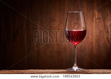 Fragile goblet of the red wine on the wooden stand on wooden wall background. Celebration and relaxation. Concept of the luxury lifestyle. Viticulture, grapes and winery. Natural material and drink. Horizontal photo.