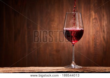 Tasty red wine poured in the elegant glass standing on the wooden stand against wooden wall background. Brightly wine and fragile goblet. Natural material and drink. Concept of the luxury lifestyle. Horizontal photo. Sommelier and tasting.