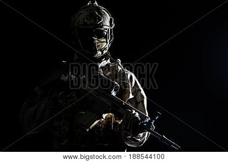 Army soldier in Protective Combat Uniform holding Special Operations Forces Combat Assault Rifle. Studio shot, dark contrast, cropped, black dark background, contour shot