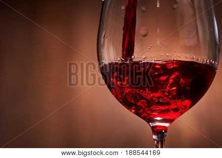 Close-up of tasty red wine pouring in the pure fragile wineglass standing against wooden background. Natural material and product. Relaxation and celebration. Horizontal photo. Viticultue, grapes and winery.
