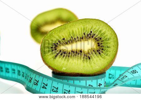 Kiwi Fruit Half Standing On Light Blue Measuring Tape Roll