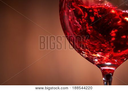 Close-up of the abstract splashing of the red wine in the fragile wineglass on the brown wooden background. Brightly tasty wine. Natural drink. Luxury lifestyle and relaxation. Still-life and backgrounds. Horizontal photo with macro.