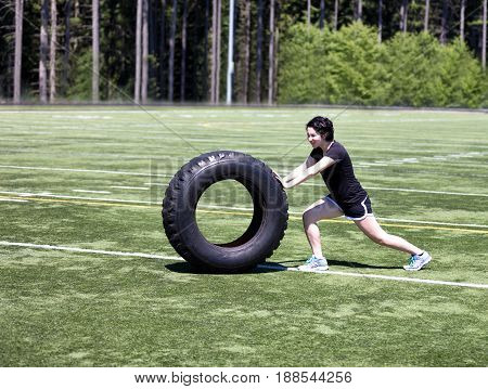 Teen age girl pushing large tire on sports field to build strength