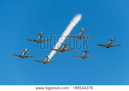 EDEN PRAIRIE MN - JULY 16 2016: Seven AT6 Texan airplanes fly overhead with single smoke trail at air show. The AT6 Texan was primarily used as trainer aircraft during and after World War II.