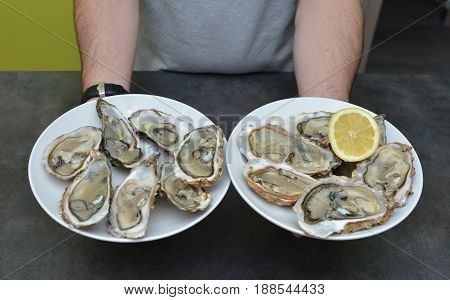 Man hands with lemon and oyster on a black background