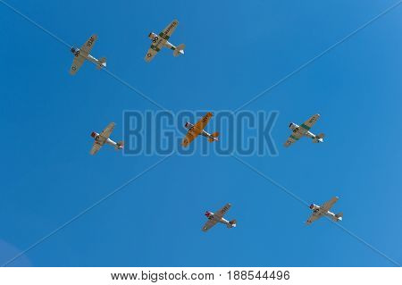 EDEN PRAIRIE MN - JULY 16 2016: AT6 Texan planes fly overhead against clear sky at air show. The AT6 Texan was primarily used as trainer aircraft during and after World War II.