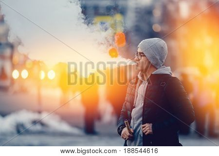 vaping man holding a mod device. cloud of vapor. Vape. high contrast and monochrome color tone.