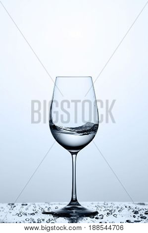 Transparent water wave in the wineglass while standing on the glass with water bubbles against light background. Environmentally friendly product. Care for the environment and health. Concept of the healthy lifestyle.