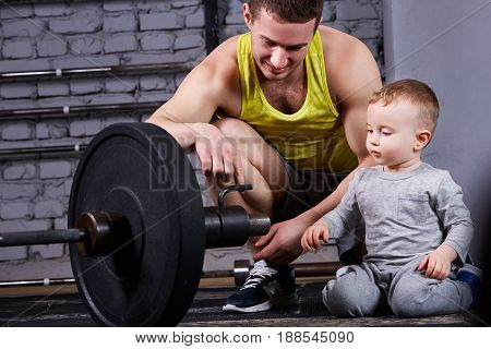 Young smiling father shows little son the dumbbell against brick wall at the cross fit gym. Sportsman and little boy in the sportwear and sportive shoes. Happy family. Rearing children in the healthy lifestyle.
