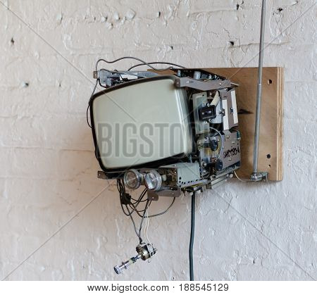 Old Television removed from case and mounted on brick wall in Hipster Loft in Dumbo Brooklyn.